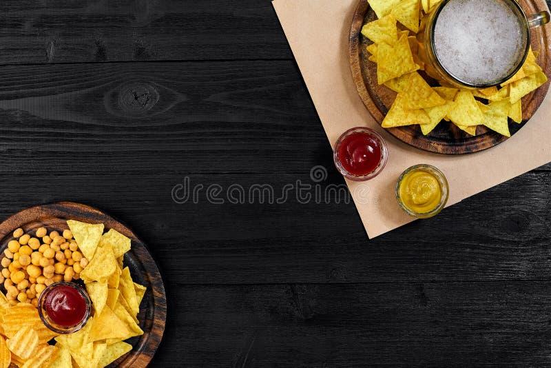 Cerveza y bocados de cerveza dorada en la tabla de madera negra Nueces, microprocesadores Visión superior con Copyspace imágenes de archivo libres de regalías