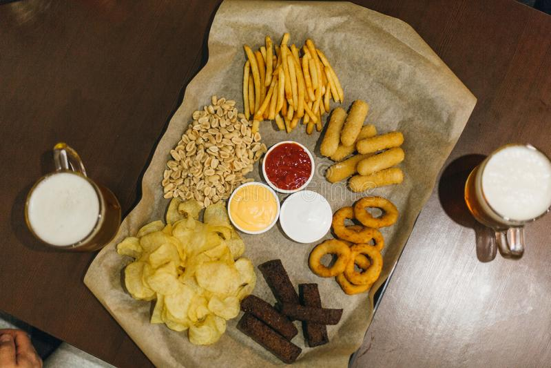Cerveza y bocados de cerveza dorada en la tabla de madera Nueces, microprocesadores, cacahuete, tostada, galletas Alimentos de pr fotografía de archivo libre de regalías