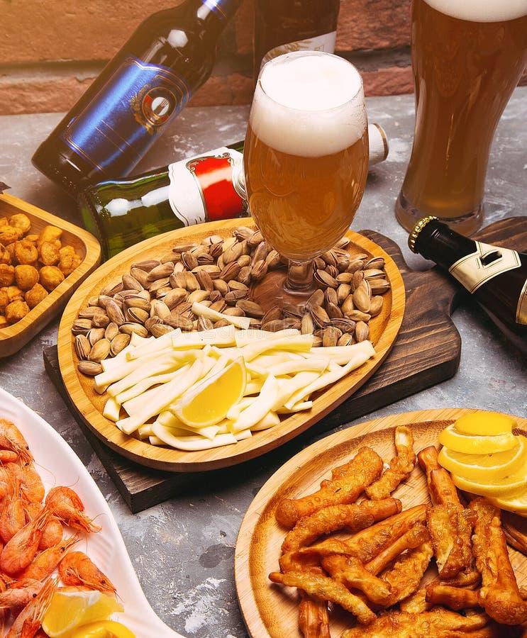 Cerveza y bocados de cerveza dorada en la tabla de madera fotos de archivo
