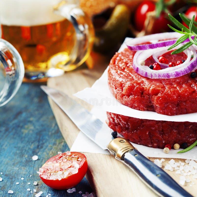 Cerveza y chuletas crudas del filete de la hamburguesa de la carne de la carne picada con el seasonin imagen de archivo