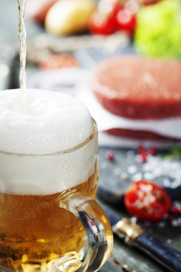 Cerveza y chuletas crudas del filete de la hamburguesa de la carne de la carne picada con el seasonin foto de archivo