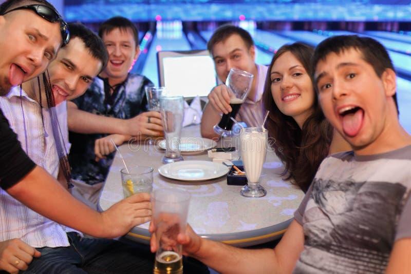 Cerveza y cocteles de la bebida de los amigos en el bowling fotografía de archivo