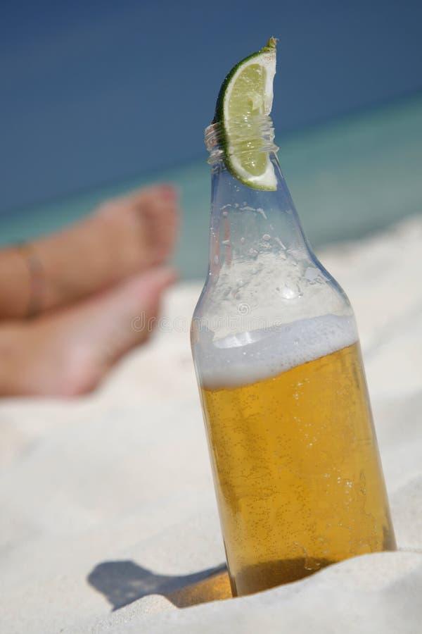 Cerveza y pies en la playa fotografía de archivo