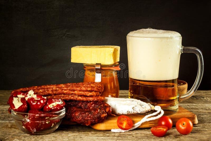 Cerveza y salchichas en una tabla de madera vieja Venta de la cerveza y de la salchicha Comida para la cerveza Comida malsana fotos de archivo