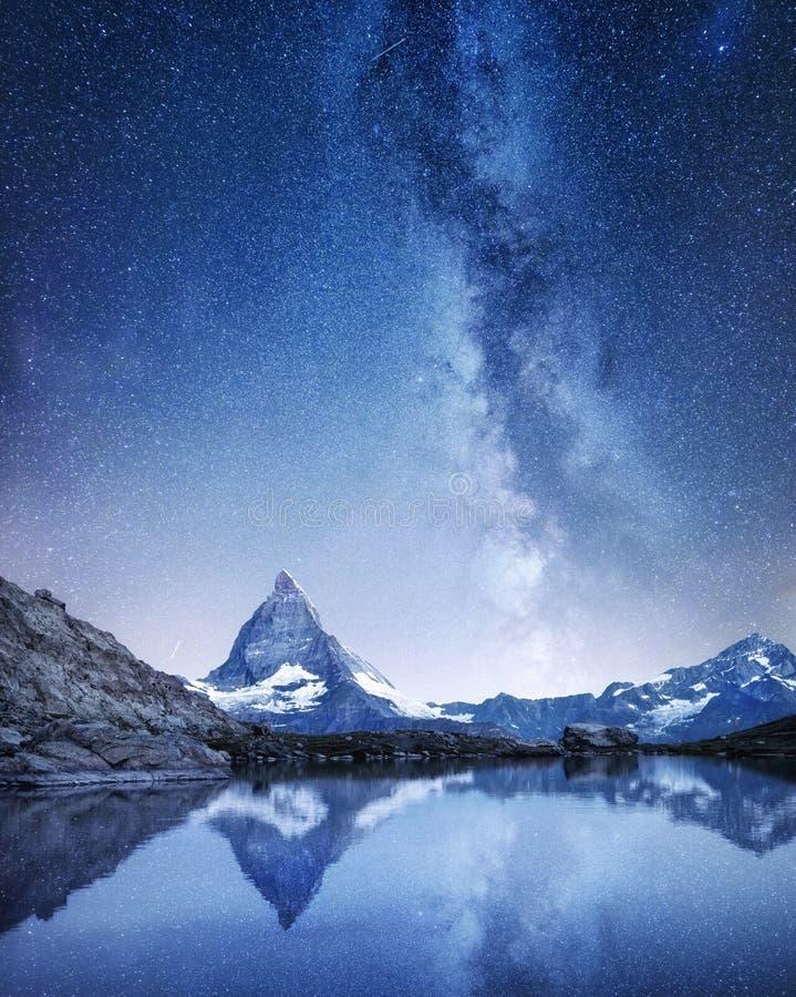 Cervino y la reflexión en el agua emergen en la noche Vía láctea sobre Cervino, Suiza foto de archivo