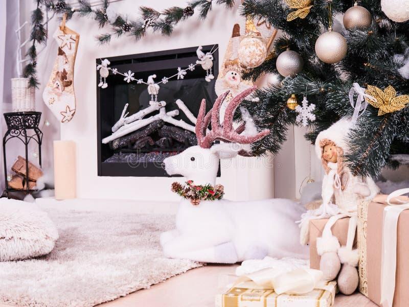 Cervos do Natal sob a árvore do ano novo com presentes, presentes Natal que armazena sobre a decoração da chaminé, cartão do ` s  imagens de stock