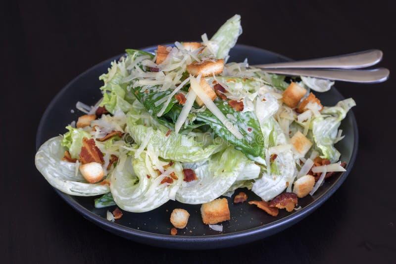 Cesar salad in black dish stock photo