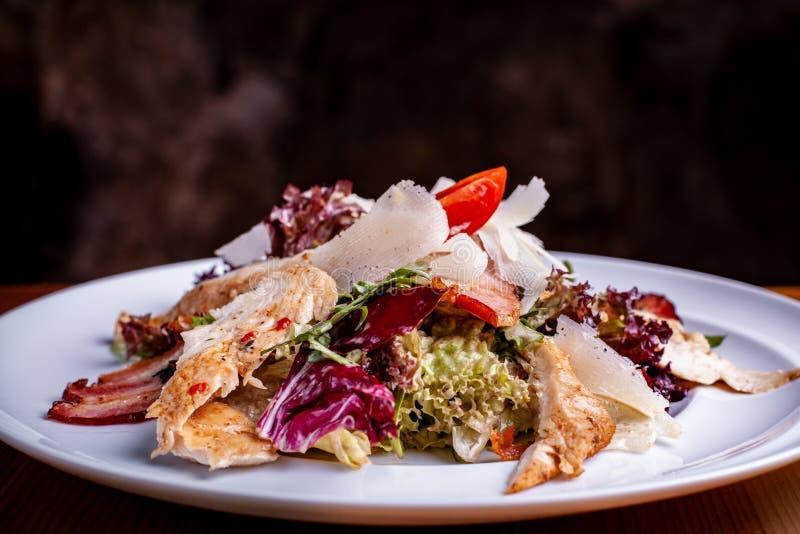 Cesar Salad en un cuenco de ensalada en un fondo del negro del restaurante imagen de archivo libre de regalías