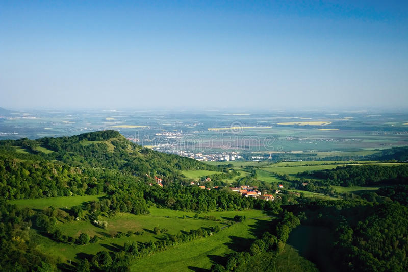 Ceske Stredohori tourist area with hill Kamyk and Litomerice city on horizont and Kundratice village in foreground in spring eveni. Ng czech landscape during stock image