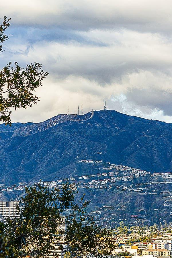 Cespugli che trascurano valle e le colline distanti con le case, cloudscape fotografia stock libera da diritti