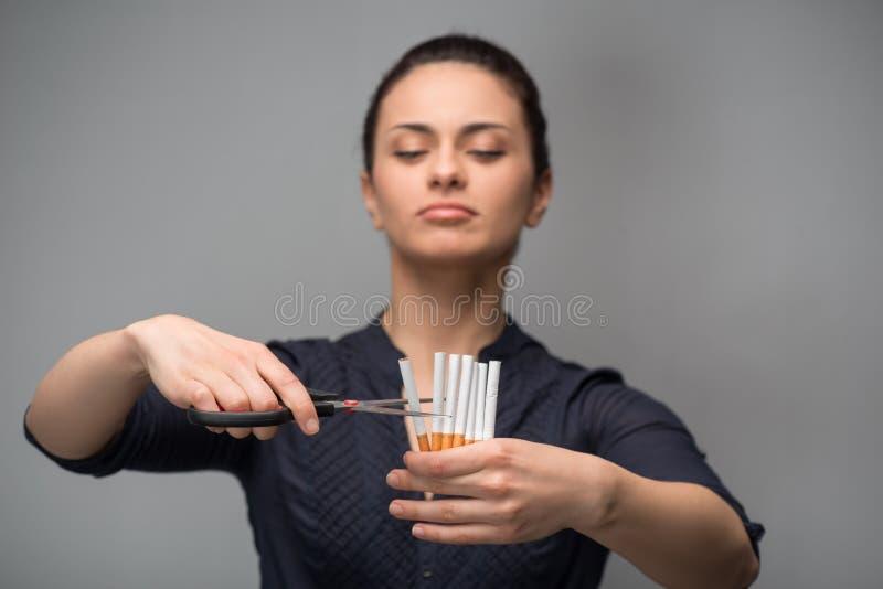 Cessez de fumer le concept Cigarettes de coupe de jeune femme images stock