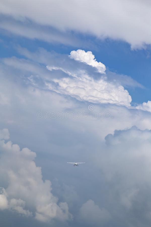 Cessnavliegtuigen die in de onweerswolk en de blauwe hemel vliegen royalty-vrije stock afbeeldingen
