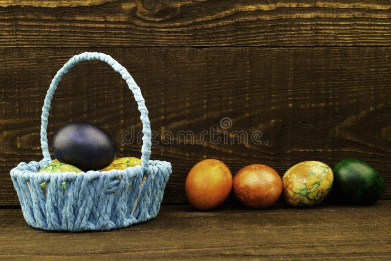 Cesta azul com os ovos da p?scoa e os ovos da p?scoa que encontram-se pr?ximo em um fundo de madeira marrom escuro, espa?o da c?p imagens de stock royalty free