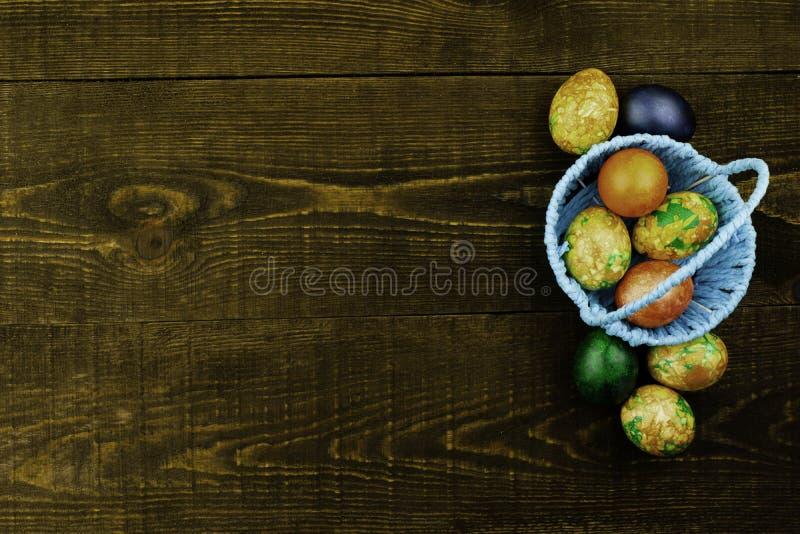 Cesta azul com os ovos da p?scoa e os ovos da p?scoa que encontram-se pr?ximo em um fundo de madeira marrom escuro, espa?o da c?p fotos de stock