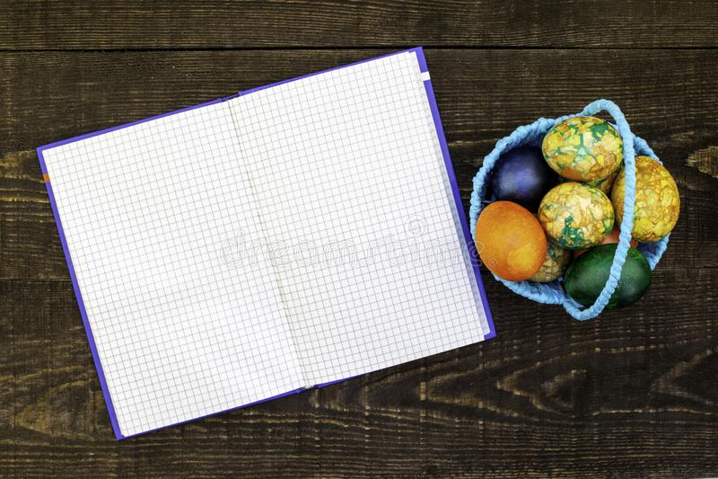 A cesta azul com ovos da páscoa em um fundo de madeira marrom escuro, desdobrou o caderno para o espaço da cópia imagens de stock royalty free
