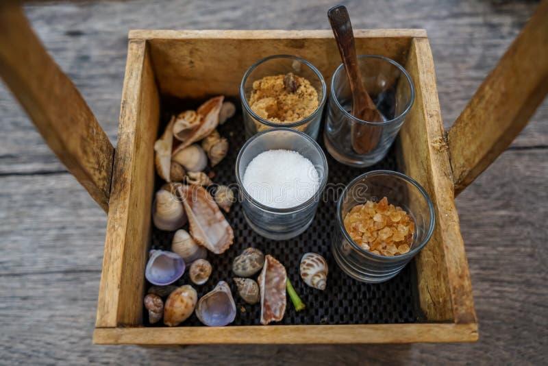 A cesta bonita da caixa de madeira do vintage que guardam vidros do açúcar e a colher para o café e o chá com mar descascam a dec imagem de stock