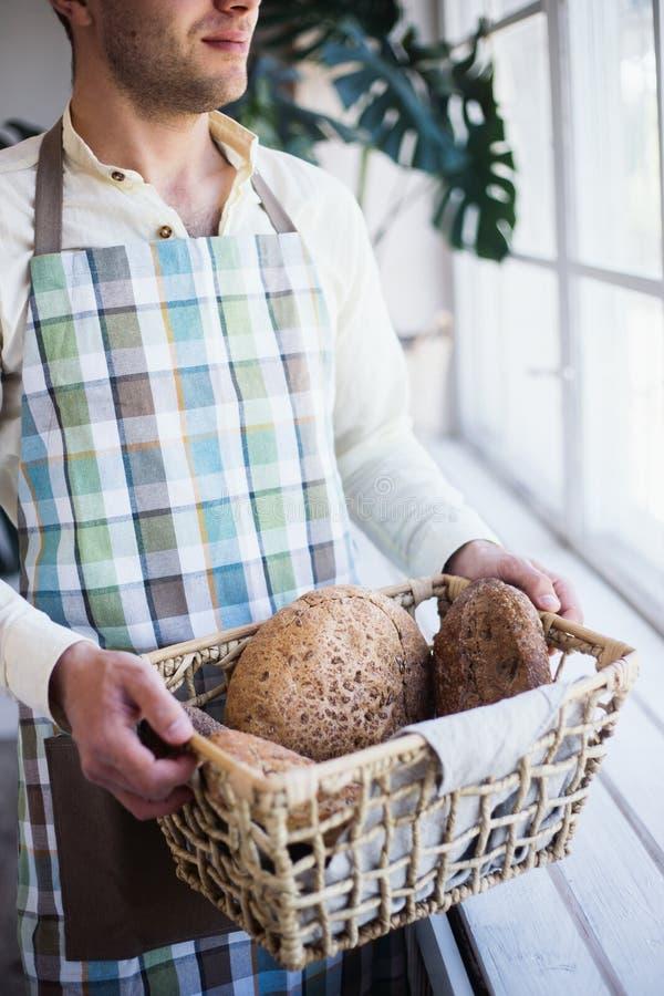 Cesta brutal de la tenencia del panadero con el pan recientemente cocido de diferentes tipos con salvado en sus manos cerca de la foto de archivo libre de regalías