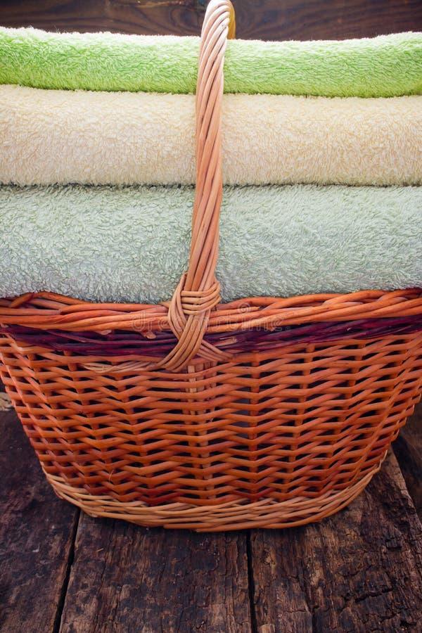 Cesta com as toalhas coloridas limpas frescas em um de madeira fotos de stock
