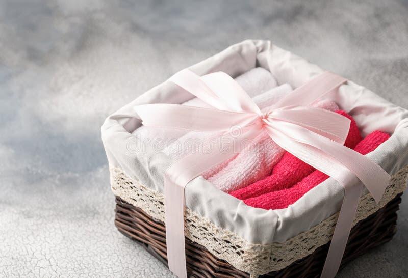 Cesta com as toalhas de banho macias no fundo cinzento fotos de stock royalty free