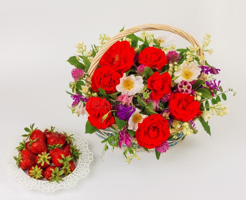 Cesta com flores e pires com morangos imagem de stock royalty free