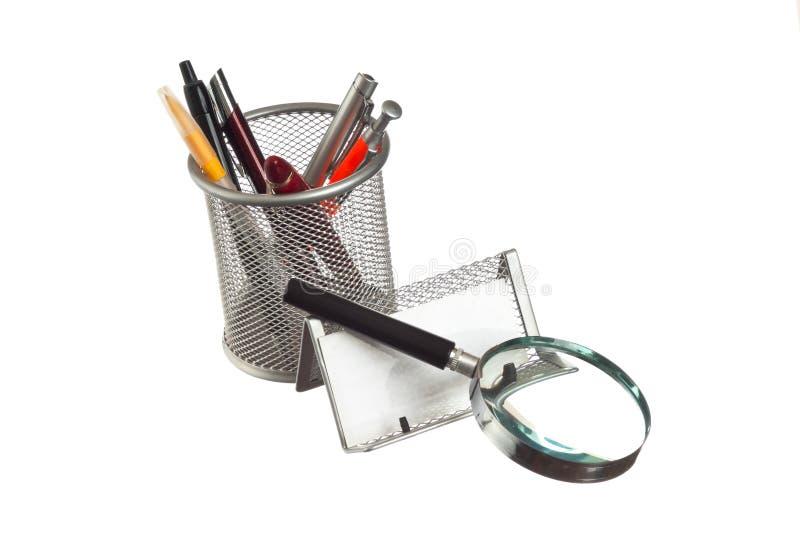 Cesta com lápis e penas no livro fotos de stock royalty free