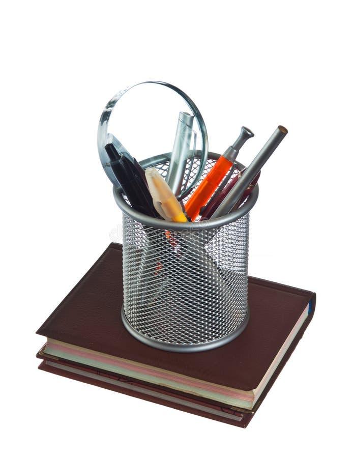 Cesta com lápis e penas no livro imagens de stock royalty free