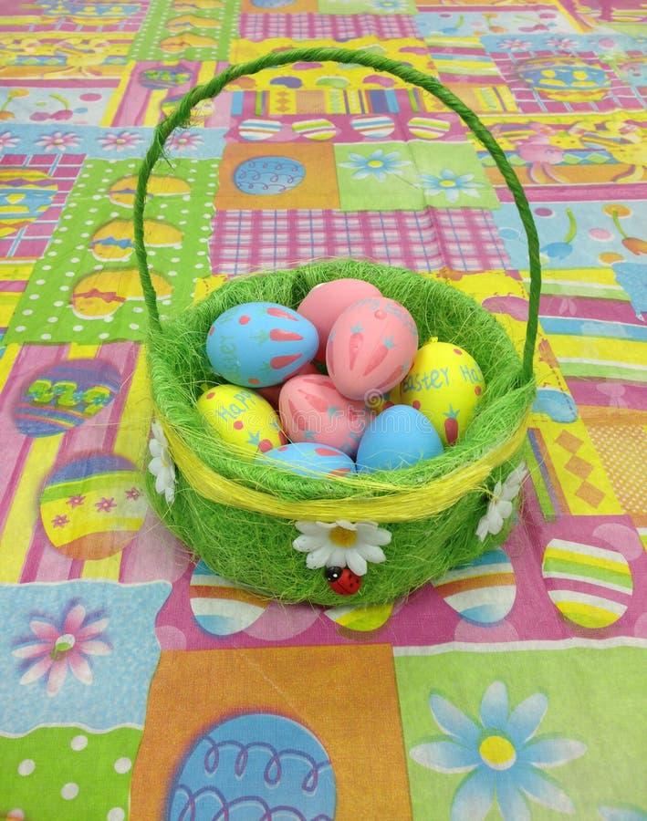 Cesta com os ovos da páscoa coloridos na tabela colorida imagem de stock
