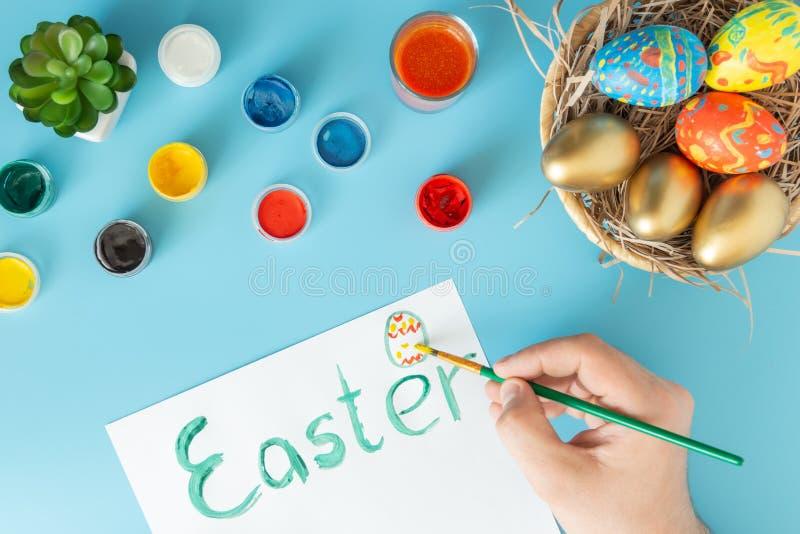 Cesta com os ovos da páscoa feitos à mão ao lado das pinturas multicoloridos e da mão com escova que pintam o ovo da páscoa no Li fotos de stock