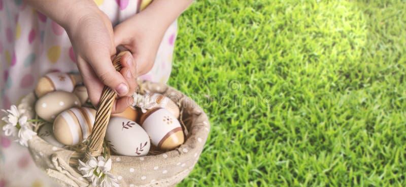 Cesta com os ovos da páscoa nas mãos da menina no fundo da grama fotografia de stock royalty free