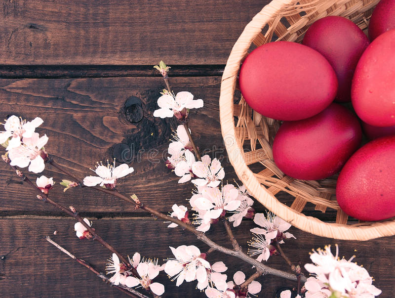 Cesta com os ovos vermelhos de easter na tabela de madeira rústica Parte traseira do feriado foto de stock royalty free