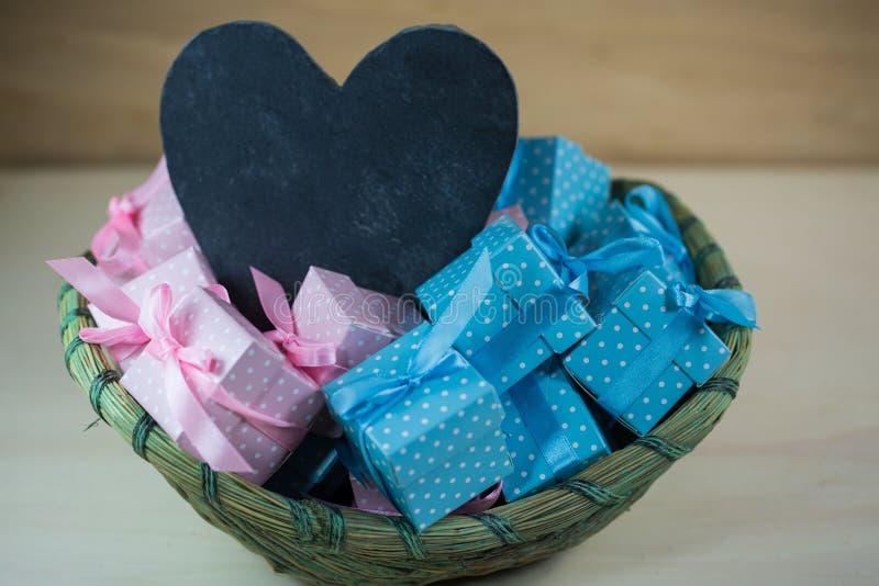Cesta com presentes pequenos, em cor-de-rosa e em azul, coração para etiquetar, b imagem de stock