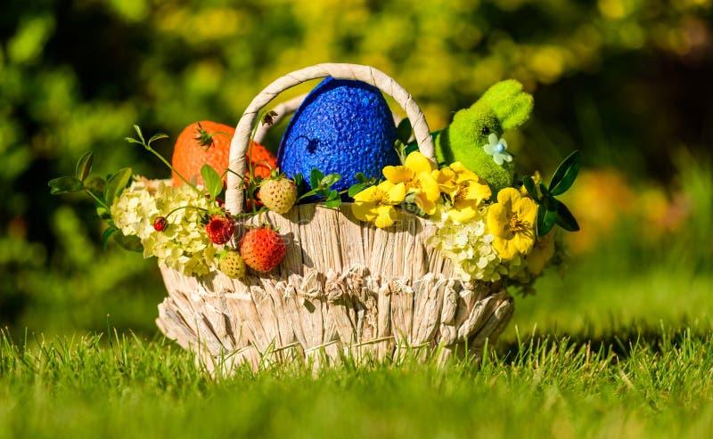 Cesta com símbolos tradicionais da Páscoa: ovos, coelho, flores e bagas coloridos imagem de stock royalty free
