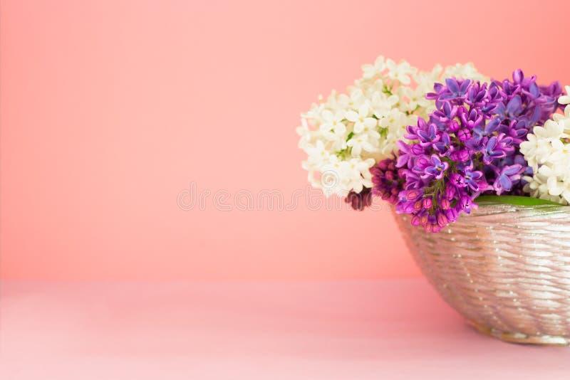 Cesta com um ramo de flores lil?s em um fundo cor-de-rosa coral Copie o espa?o Ramalhete bonito do ver?o imagens de stock royalty free