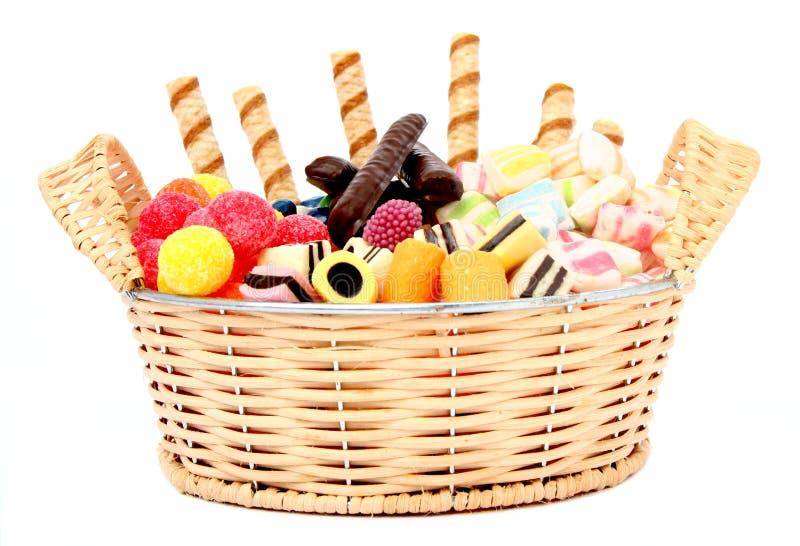 Cesta com vários doces e os bolinhos, isolados fotografia de stock