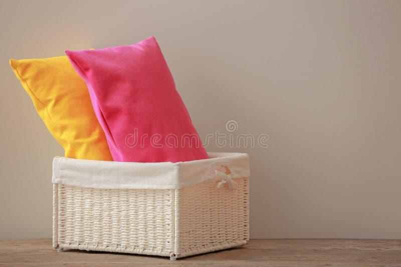 Cesta con las almohadas en la tabla de madera contra fondo gris imagenes de archivo