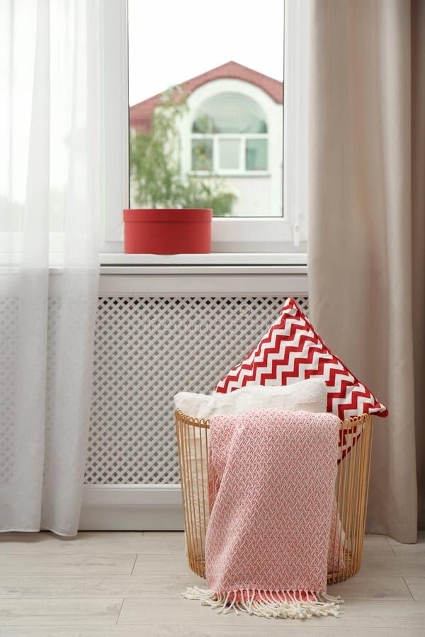 Cesta con las almohadas y la tela escocesa cerca de la ventana en sitio imagenes de archivo