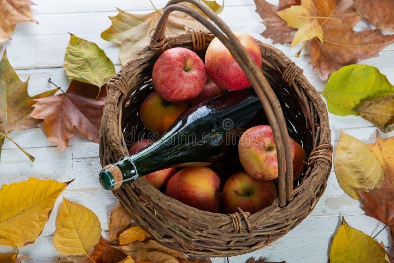 Cesta con las manzanas y la botella hermosas de sidra, en las hojas de otoño imágenes de archivo libres de regalías