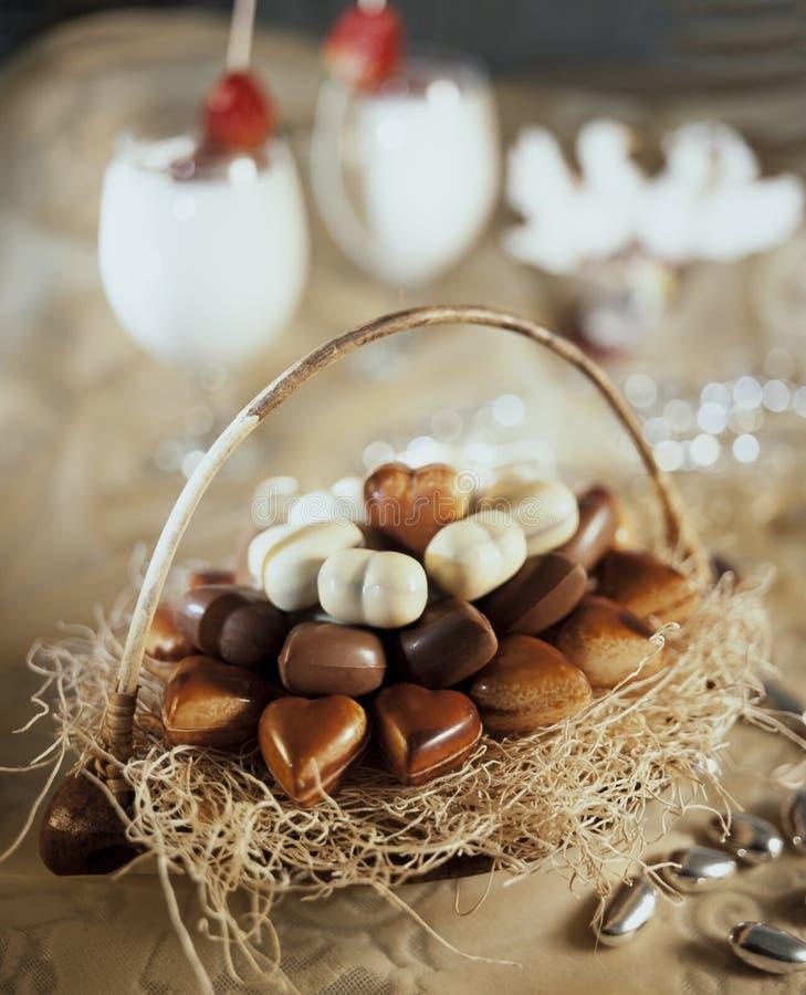 Cesta con los chocolates en forma de corazón con dos vidrios todavía del coktail de vida imágenes de archivo libres de regalías
