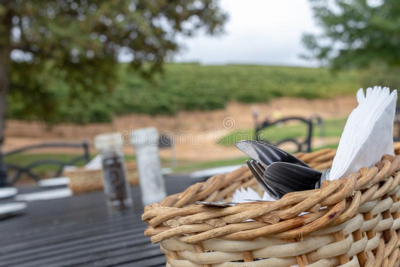 Cesta con los cubiertos en primero plano, fuera del paisaje de la granja del foco imagen de archivo