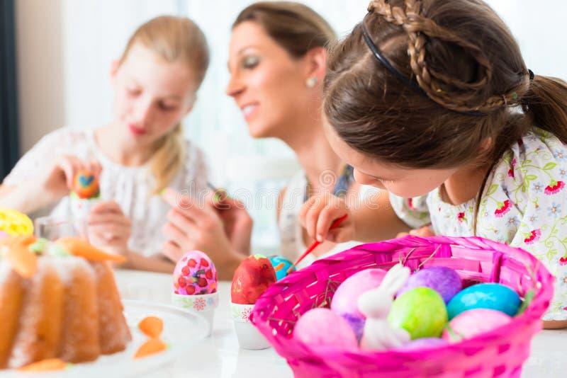Cesta con los huevos de Pascua que son coloreados por la familia foto de archivo libre de regalías