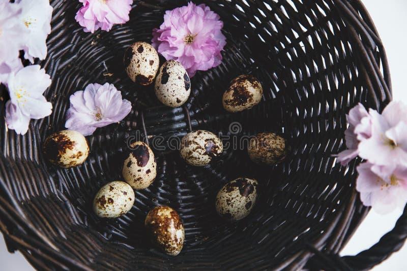Cesta con los huevos y las flores imagenes de archivo