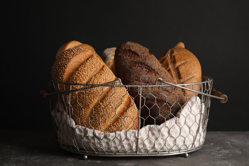 Cesta con pan fresco en la tabla contra negro imagen de archivo libre de regalías