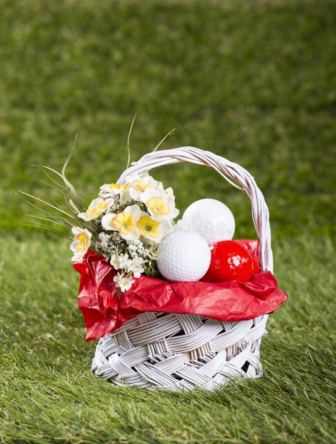 Cesta da Páscoa com bolas de golfe e flores foto de stock