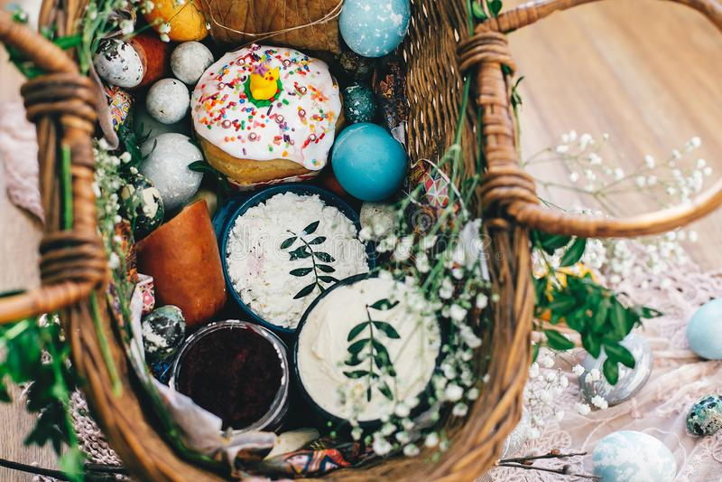Cesta da Páscoa com ovos, pão de easter, presunto, salsicha, manteiga com flores e ramos no pano no fundo de madeira rústico feli imagens de stock