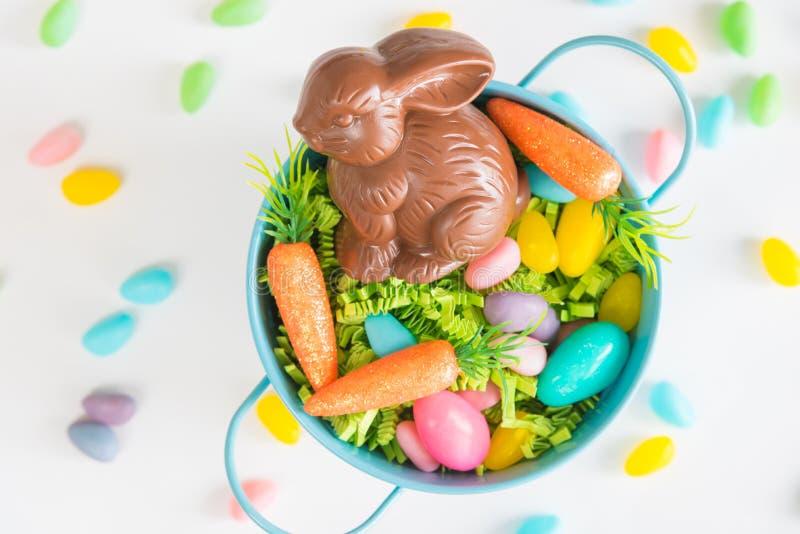 Cesta da Páscoa enchida com a grama da Páscoa, os ovos de doces, as mini cenouras, e um coelho do chocolate foto de stock royalty free