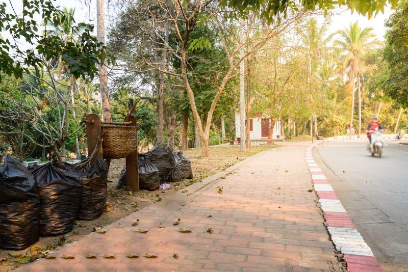 A cesta de bambu e o uso preto do saco para mantêm o lixo perto do walkpath no jardim fotografia de stock