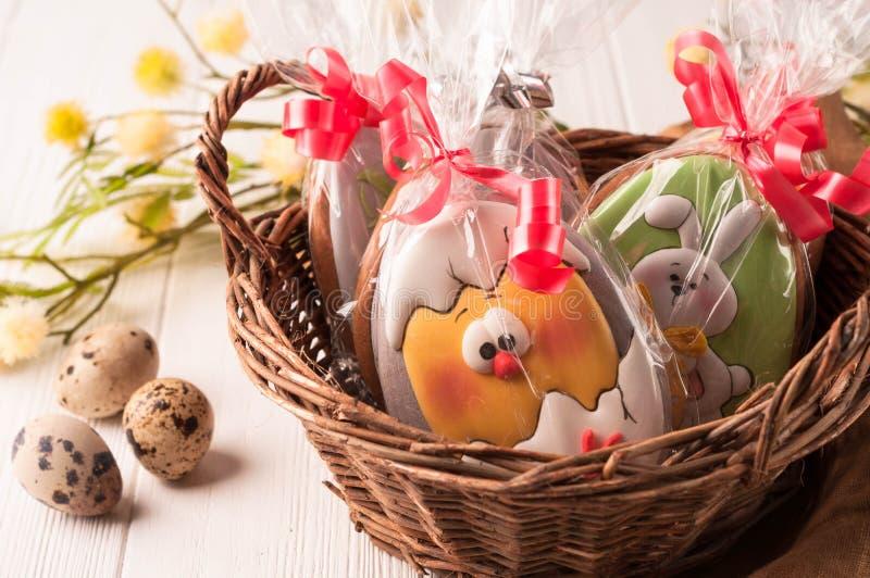 Cesta de Brown com as cookies envolvidas de easter perto dos ovos de codorniz e do ramo de florescência fotos de stock royalty free