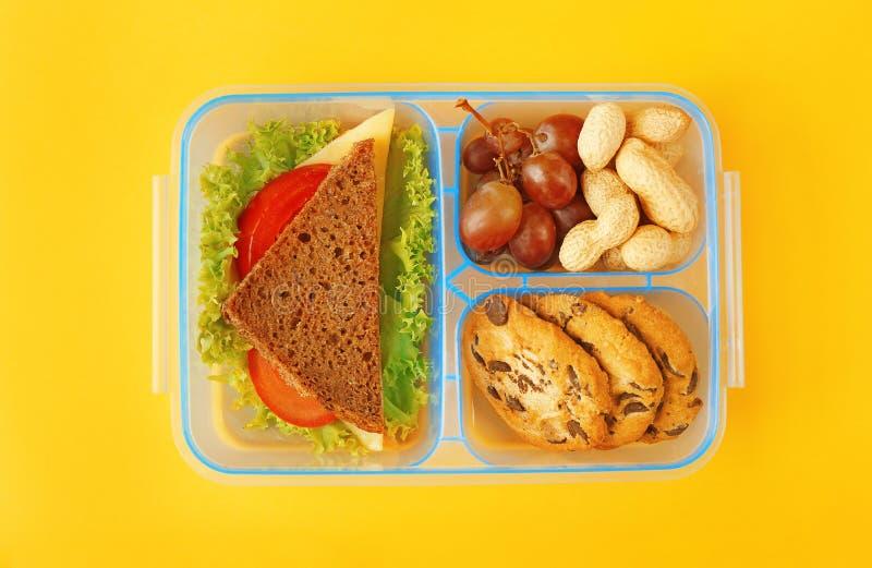 Cesta de comida com o jantar no fundo amarelo imagem de stock royalty free