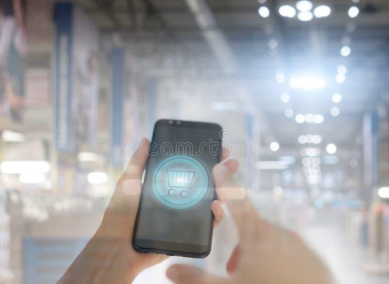Cesta de compras en una pantalla del teléfono móvil Mano de la mujer que sostiene el teléfono móvil en fondo de la falta de defin fotografía de archivo libre de regalías
