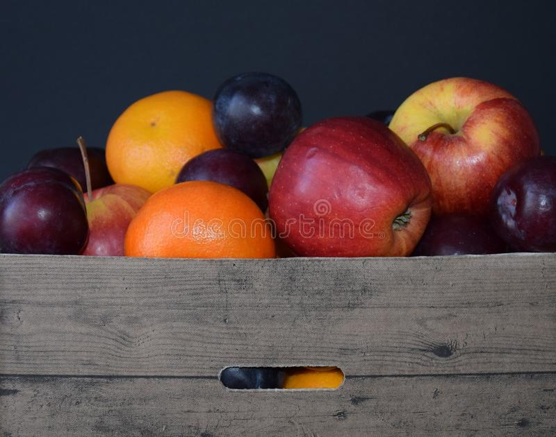 Cesta de fruta con la manzana, el orangen y el ciruelo foto de archivo